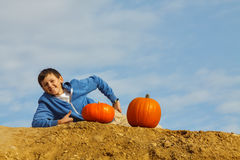 Smiling boy with two pumpkins. A boy with two pumpkins on blue sky royalty free stock images