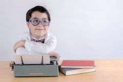 Smiling boy with typewriter. On white background stock photo