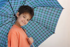 A smiling boy with an umbrella. A smiling boy holding an open umbrella isolated on a white background Stock Images