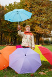Smiling boy with umbrellas in autumn park Stock Photography
