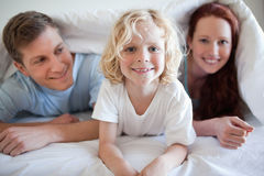 Smiling boy under the cover with his parents Royalty Free Stock Photo