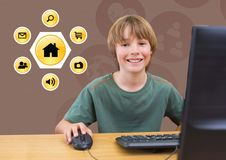 Smiling boy using desktop pc with various application icons in background. Digital composition of a smiling boy using desktop pc with various application icons Royalty Free Stock Photo