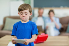 Smiling boy using digital tablet in living room Royalty Free Stock Images