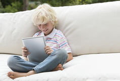 Smiling boy using digital tablet on outdoor sofa Royalty Free Stock Images