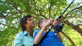 Smiling boy using a fishing rod while being helped by his father Royalty Free Stock Photos