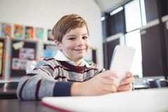 Smiling boy using mobile phone at desk. Portrait of smiling boy using mobile phone at desk in school Stock Photo