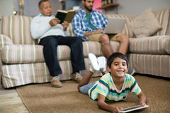 Smiling boy using tablet while lying on carpet with father and grandfather in background. Smiling boy using tablet lying on carpet with father and grandfather Stock Images