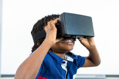 Smiling boy using virtual reality headset in classroom. Smiling boy using virtual reality headset while sitting in classroom Stock Photography