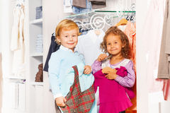 Smiling boy with vest and girl shopping together. Smiling boy with vest and girl with sweater  are together while shopping in the clothes store Royalty Free Stock Images