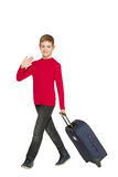 Smiling boy walking and waving hello holding travel bag Royalty Free Stock Photo