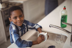 Smiling boy washing cup in kitchen sink. Portrait of smiling boy washing cup in kitchen sink at home stock photography