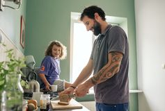 Smiling boy watching his father make lunch in their kitchen royalty free stock photography