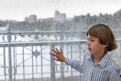 Smiling boy watching the rain outside at a window Stock Photos