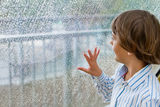 Smiling boy watching the rain outside at a window. Smiling little boy watching the rain outside at a window Royalty Free Stock Photo
