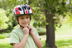 Smiling boy wearing bicycle helmet at park Royalty Free Stock Photos