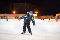 Smiling boy wearing in black suit and blue hat skates. At dark winter night stock photography