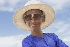 Smiling boy wearing a boater straw hat and a pair of sunglasses Royalty Free Stock Photos