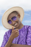 Smiling boy wearing a boater straw hat and a pair of sunglasses Stock Photo