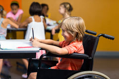 Smiling boy on wheelchair using digital tablet Royalty Free Stock Images