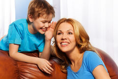 Smiling boy whispering a secret to mother. Portrait of happy boy whispering a secret to his mother and standing behind the back of the sofa Stock Photo