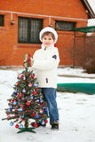 Smiling boy in white jacket with plastic Cristmas tree Royalty Free Stock Image