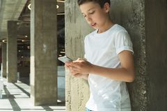 Smiling boy in white T-shirt and stands indoor and uses smartphone. Boy plays computer games on digital gadget. Royalty Free Stock Photos