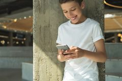 Smiling boy in white T-shirt and stands indoor and uses smartphone. Boy plays computer games on digital gadget Stock Photo