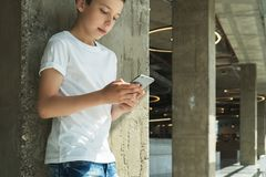 Smiling boy in white T-shirt and stands indoor and uses smartphone. Boy plays computer games on digital gadget Royalty Free Stock Photo