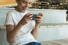 Smiling boy in white T-shirt and sunglasses sitting indoor and uses smartphone. Teenager plays computer games Royalty Free Stock Photo