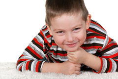 Smiling boy on the white thick carpet Royalty Free Stock Image