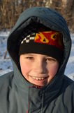 Smiling boy in winter clothes. On a background of the winter forest Stock Photos