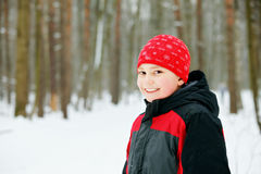 Smiling boy in winter forest Royalty Free Stock Images