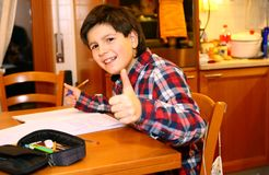 Smiling BOY writes on his notebook Stock Images