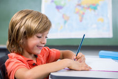 Smiling boy writing on book in classroom Stock Photos