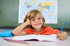 Smiling boy writing on book in classroom at school Royalty Free Stock Photos