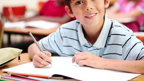 Smiling boy writing on his notebook stock video footage