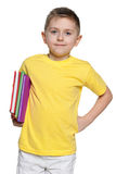 Smiling boy in yellow shirt with books Royalty Free Stock Photography