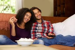 Smiling boyfriend and girlfriend relaxing watching tv Stock Images