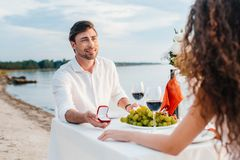 Smiling boyfriend making propose with ring to girlfriend. In romantic date outdoors royalty free stock photo