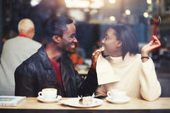 Smiling boyfriend wiping mouth with a napkin his girlfriend during breakfast in modern coffee shop interior Royalty Free Stock Images