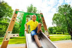 Smiling boys with bending knee on chute Stock Photography