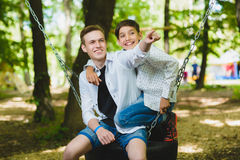 Smiling boys having fun at playground. Children playing outdoors in summer. Teenagers riding on a swing outside Stock Image