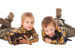 Smiling boys holding puppies lie on the floor Stock Photo