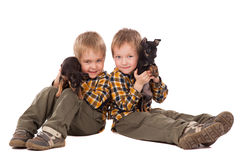 Smiling boys holding puppies lie on the floor Stock Images