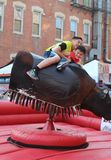 Smiling Boys Ride Mechanical Bull at Mexican Street Festival in Chicago Stock Photography