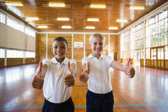 Smiling boys showing thumbs up in school gym. Portrait of boys showing thumbs up in school gym Stock Images