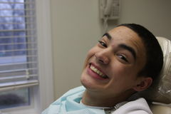 Smiling without braces. A teen guy smiling happily without his braces in a dentists clinic Royalty Free Stock Image