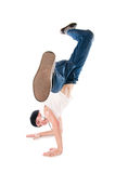 Smiling breakdancer. Young happy breakdancer standing upside down on hands with a flying kick stock photography
