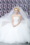 Smiling bride. 20 yeared bride in white wedding dress with veil is smiling and sitting on a bench Stock Photos