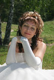 Smiling bride. Bride sits on lawn in park Royalty Free Stock Photos